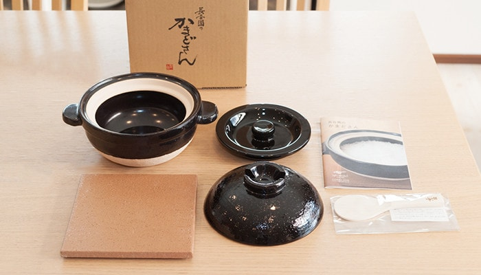 A set of Kamado-san. From the top left to right, donabe rice cooker, inner lid, introduction. Form the bottom left to right, ceramic pot mat, outer lid, and Miyajima Shakushi.