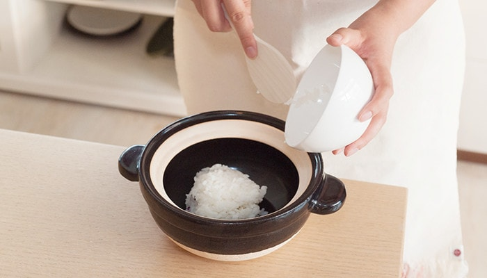 A woman is putting leftover rice into Kamado-san