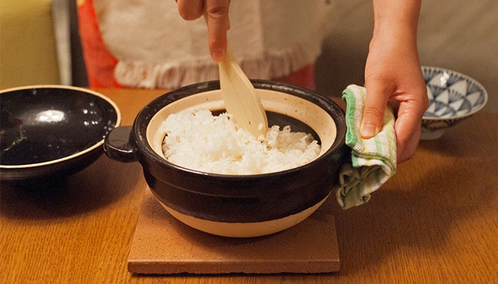 A woman is stirring cooked white rice