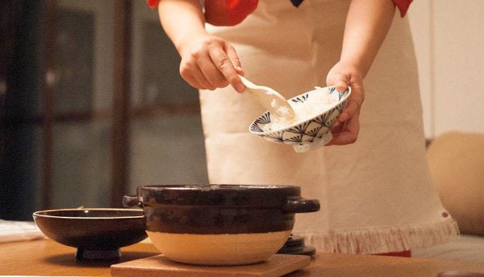 A woman is serving cooked white rice into a rice bowl