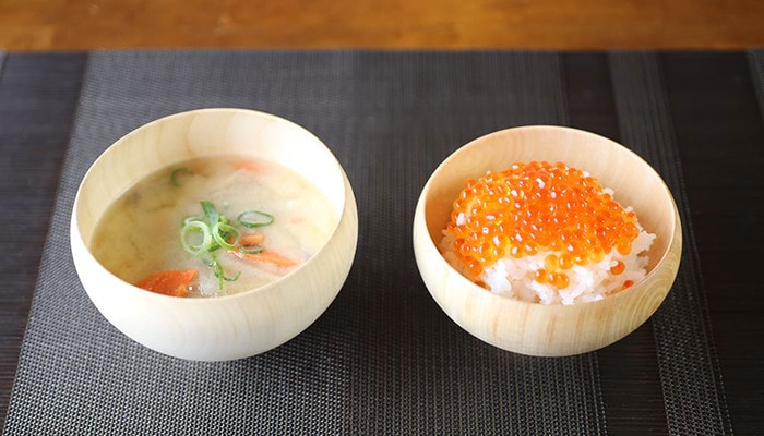 Miso soup and rice with salmon in wooden bowl