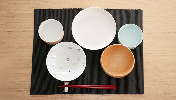 Japanese table setting with a flat rice bowl, a wooden soup bowl, and three Arita porcelain