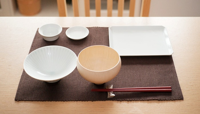 Japanese table setting with a rice bowl, a wooden soup bowl, and three Arita porcelain plates