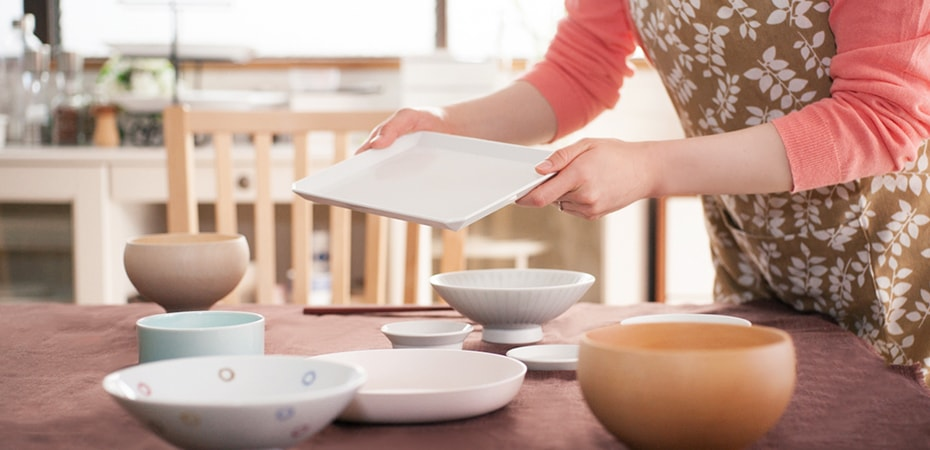 A woman is making a table setting with Square plate