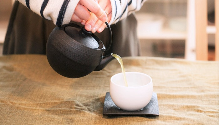 Pouring Japanese green tea into a teacup