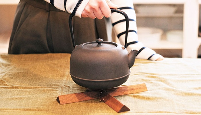 A woman hold a Nanbu cast iron kettle