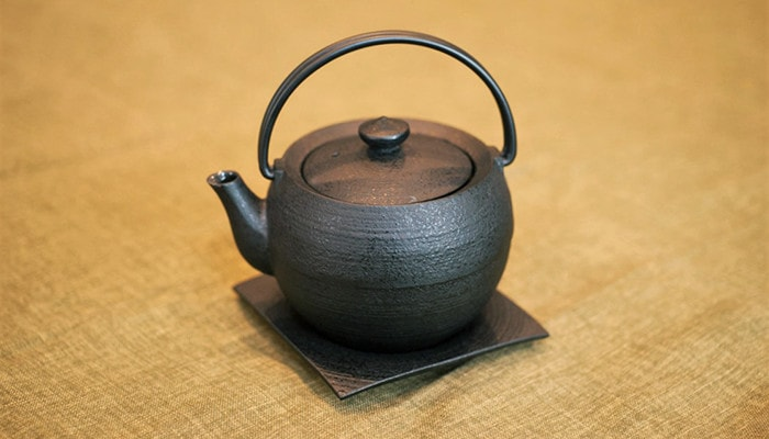 Cast iron teapot on a saucer from Chusin Kobo