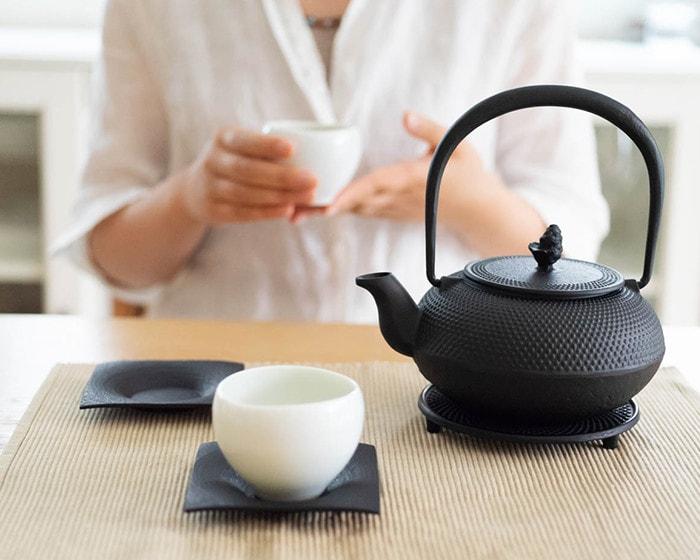 テーブルにRojiの南部鉄瓶とお茶セットが置いてあり、奥で女性がお茶を飲んでいる様子