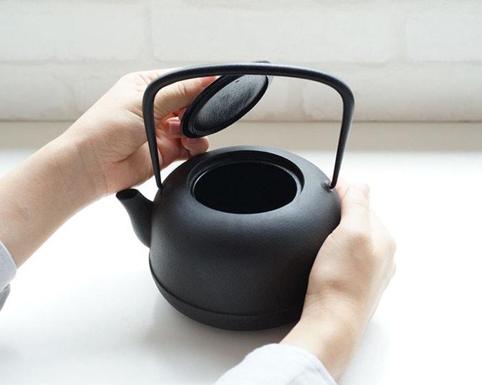 A woman holds Nanbu tetsubin and opens its lid