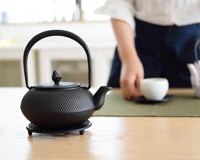 Roji南部鉄瓶がテーブルに置かれており奥では女性がお茶の支度をしている様子
