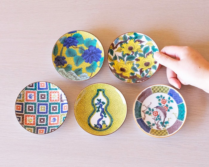 A woman takes a Kutani ware plate of Masterpiece collection of Ko Kutani