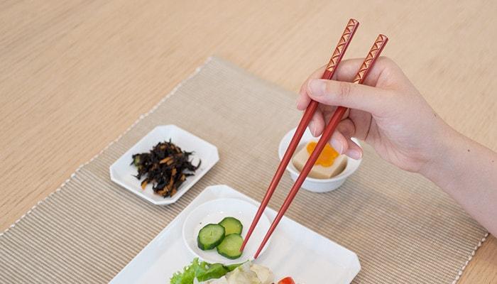 A woman has Wajima lacquer chopsticks from Hashimoto Kousaku Shikkiten
