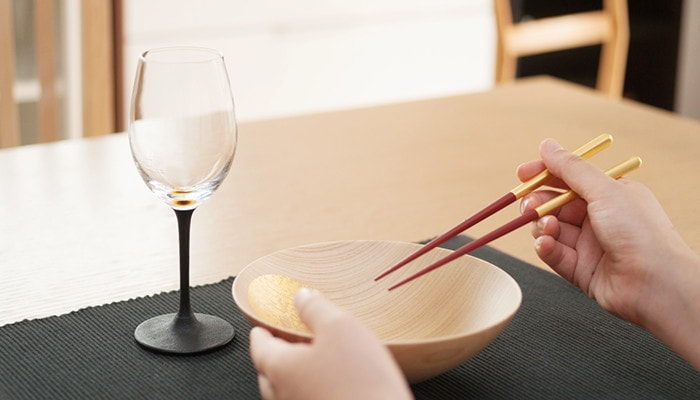 A woman has Oborozuki bowl and chopsticks from Hakuichi, and lacquer wine glass on the table