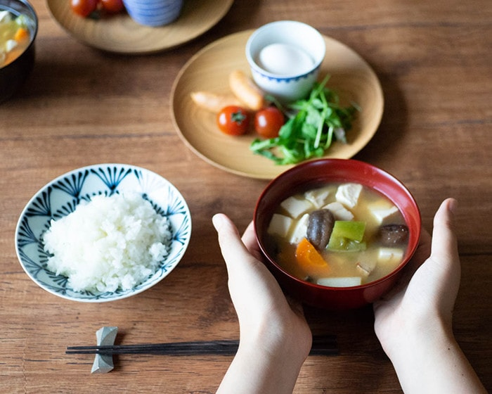 Wrap Gudakusan Shiru Wan with miso soup with hands on dinner table