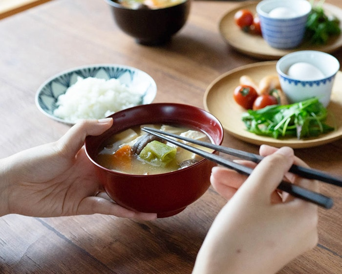 A woman eats miso soup with lacquerware bowl
