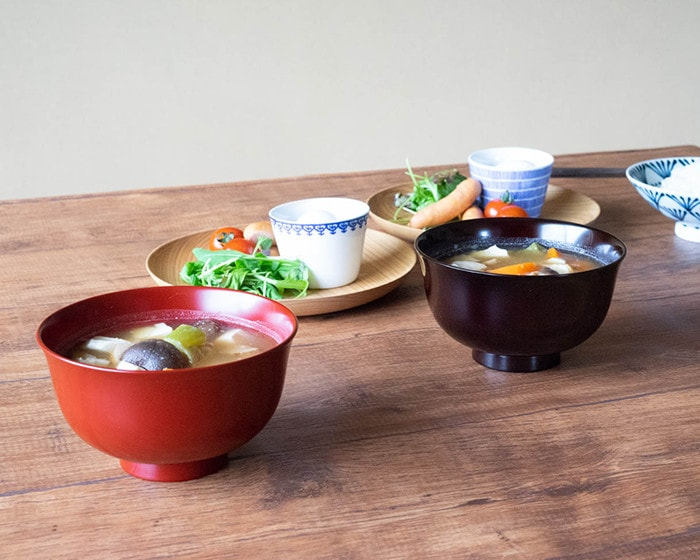 Lacquerware bowls with miso soup and other meals on dinner table