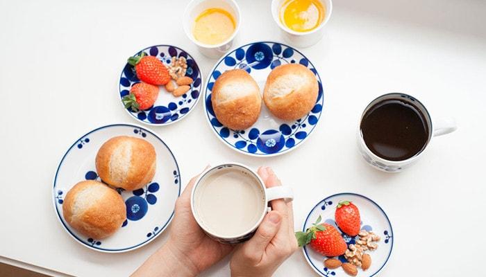 白山陶器のブルームの食器にパンやイチゴ、ナッツが乗っていて、飲み物の入ったカップを女性が持っている