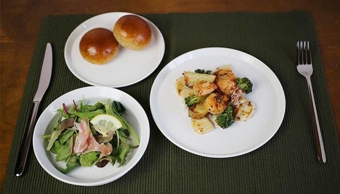 サラダやパン、野菜とエビの炒めものがラウンドプレートに乗っている