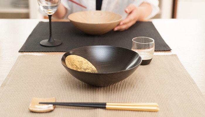 テーブルに箔一のおぼろ月や箸セット、鳥羽漆芸のうるしの酒器が乗っている