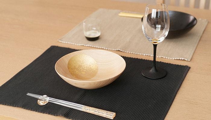 テーブルに箔一のおぼろ月や箸セット、鳥羽漆芸のうるしの酒器がセッティングされている