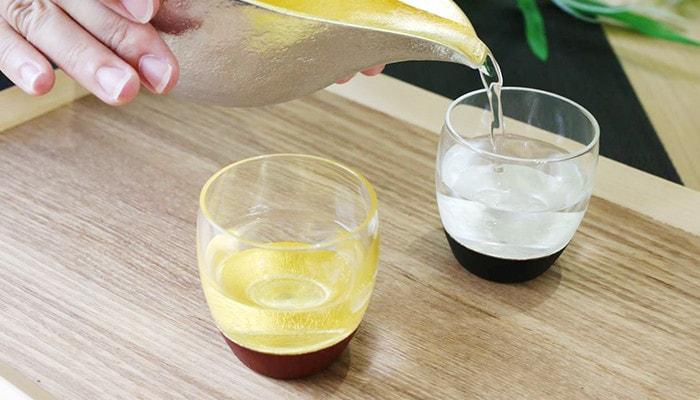 鳥羽漆芸のうるしの酒盃に能作の片口でお酒を注いでいる様子