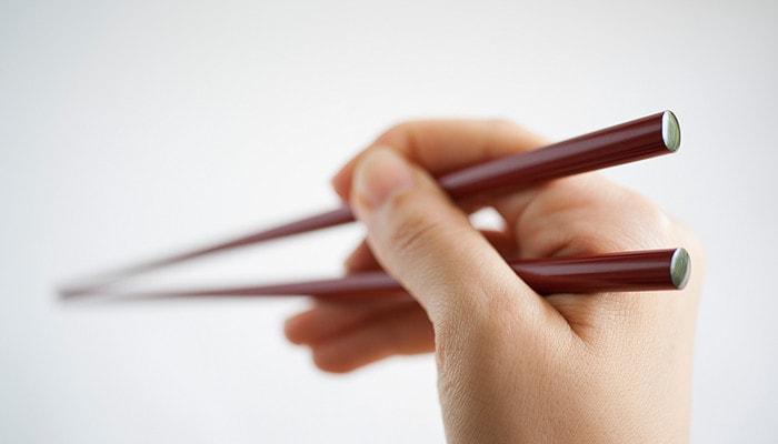 輪島キリモトの楕円箸を女性が持っている様子