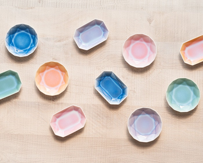 There are colorful ARITA JEWEL plates on the table