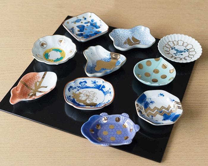 お菓子が乗っているKIHARAの豆皿が3枚あり、そのうちの1つを女性が手に持っている様子