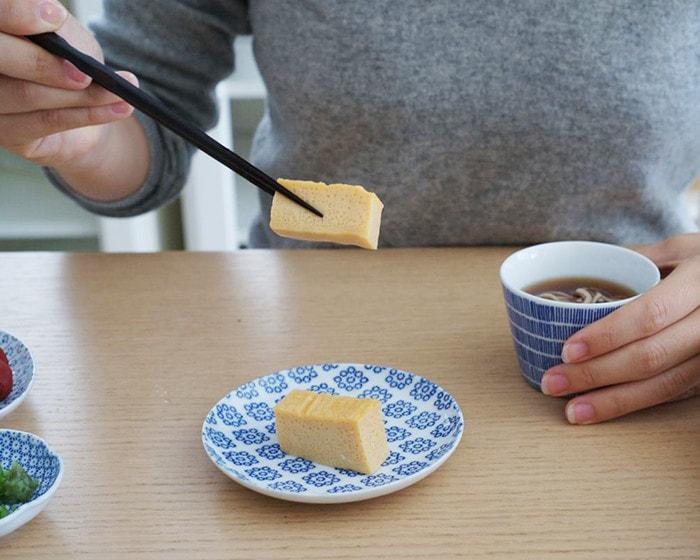 女性が左手で蕎麦のはいった東屋のそば猪口を持っていて、右手で出し巻たまごを箸で掴んでいる様子