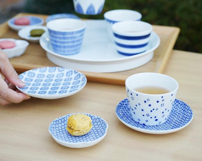 1616aritajapanのラウンドプレートにお茶の入った東屋の蕎麦ちょこや、キウイの乗った豆皿、スプーンが乗っている