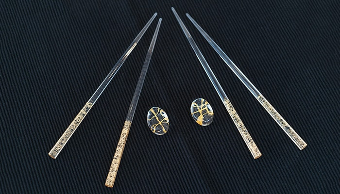 2 pairs of Clear gold thread chopsticks on the navy place mat