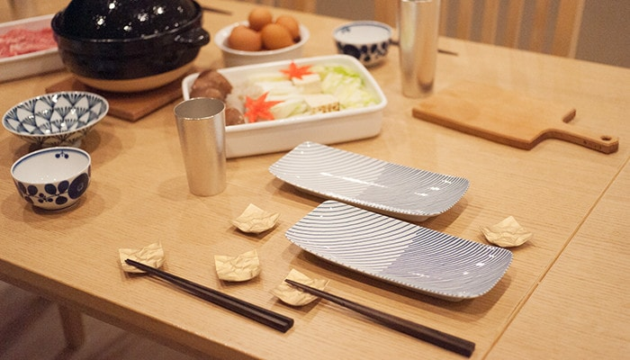 テーブルにセッティングされた重ね縞のお皿や箸置きなど
