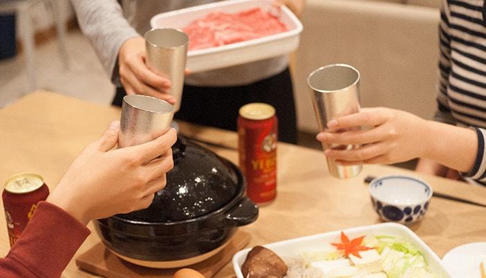 テーブルを囲んだ3人の人たちがビアカップをもって乾杯をしている様子