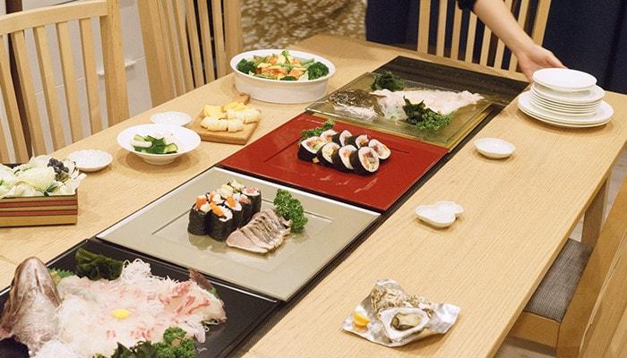 折敷に乗ったお寿司やお刺身や、サラダなどが食卓に並んでいる様子