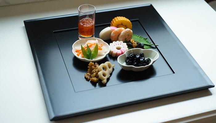 折敷におせち料理が綺麗に盛り付けられている