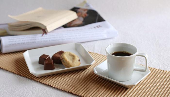 コーヒーの入ったコーヒーカップとお菓子の乗ったスクエアプレート、奥には本や雑誌が置かれている
