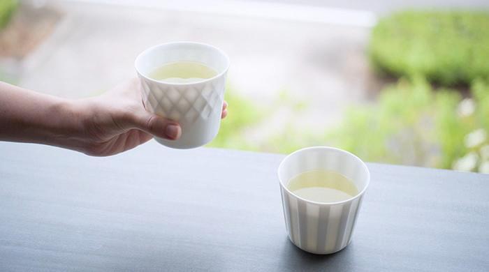 お茶の入った小田陶器のHONOKAが2つ。ひとつは女性が手に持っている