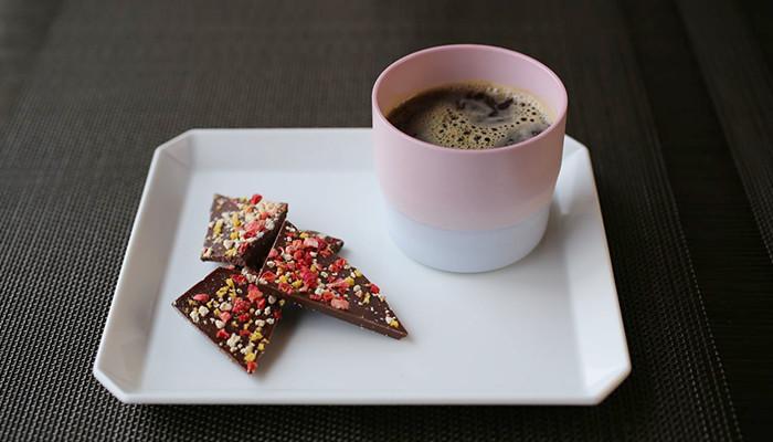 スクエアプレートの上にチョコとコーヒーの入ったピンク色のエスプレッソカップ