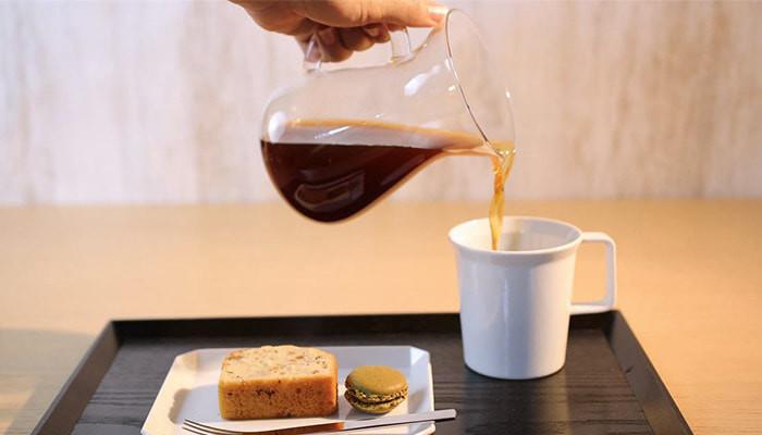ケーキやマカロンが乗ったスクエアプレートと、奥で1616/arita japanのマグカップにコーヒーを注いでいる様子