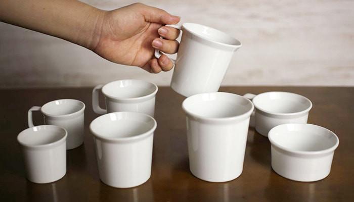8種類の1616/arita japanのマグやティーカップが並んでいてそのうちのひとつを持っている様子