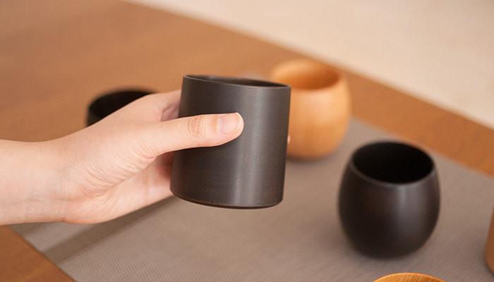 我戸幹男商店の木製カップが机に並んでいて、ひとつを手に持っている