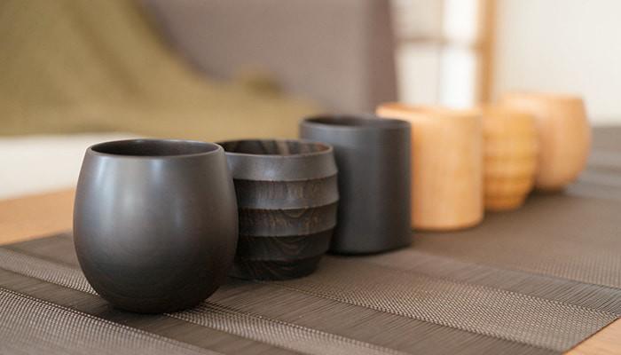 我戸幹男商店の木製カップが机に1列に並んでいる