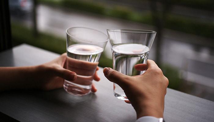 水の入ったワイヤードビーンズのMIZUグラスで乾杯している様子