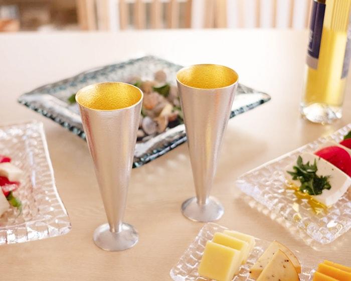 テーブルの上に2つロックグラスとお菓子の乗った小皿が乗っていて、そのうち1つのロックグラスを女性が持っている
