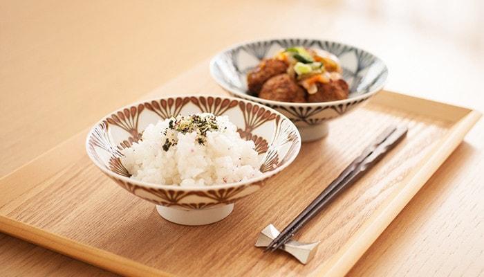 ご飯とおかずをそれぞれ盛り付けた平茶碗と箸セットがお盆に乗っている