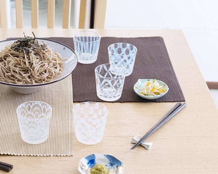 蕎麦が盛りつれられたkasumiボウルのまわりに廣田硝子の蕎麦ちょこやamabroの豆皿が並んでいる