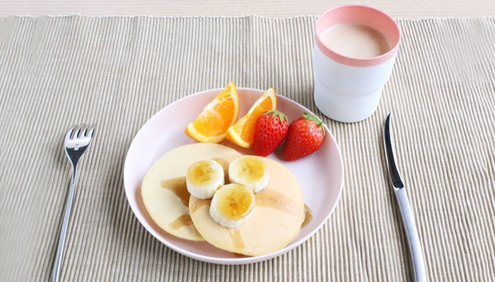 Here is the pancakes and fruits on a light pink plate. Have a coffee with pink lined white mug