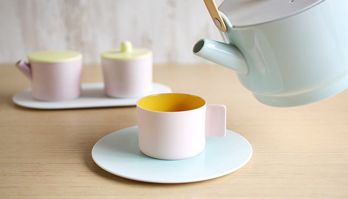 Pouring tea into a light pink cup with light blue saucer. Behind the cup. there is a light pink sugar and creamer set