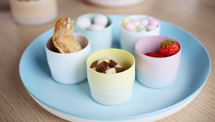There are pastel colored espresso cups with colorful confectionery and fruits on a light blue plate.