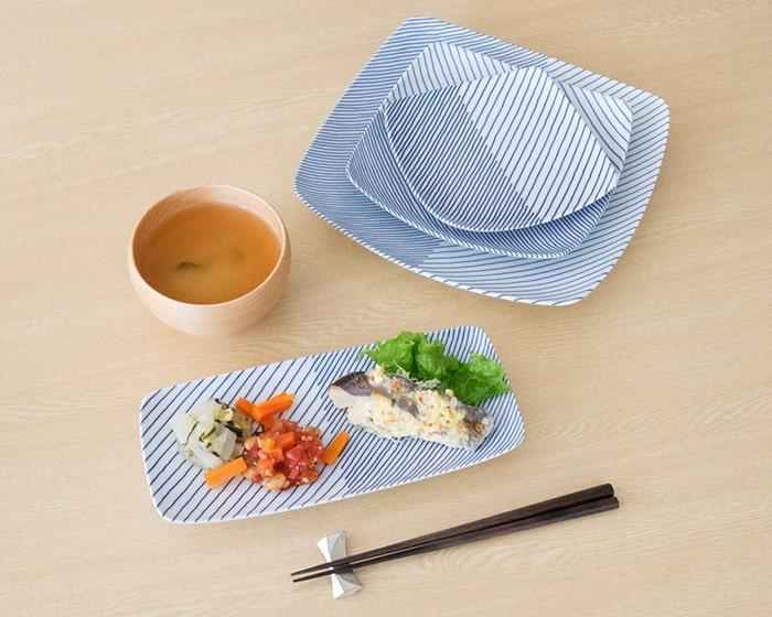 焼き魚とお惣菜を盛り付けた白山陶器の長皿と3枚重ねた角皿